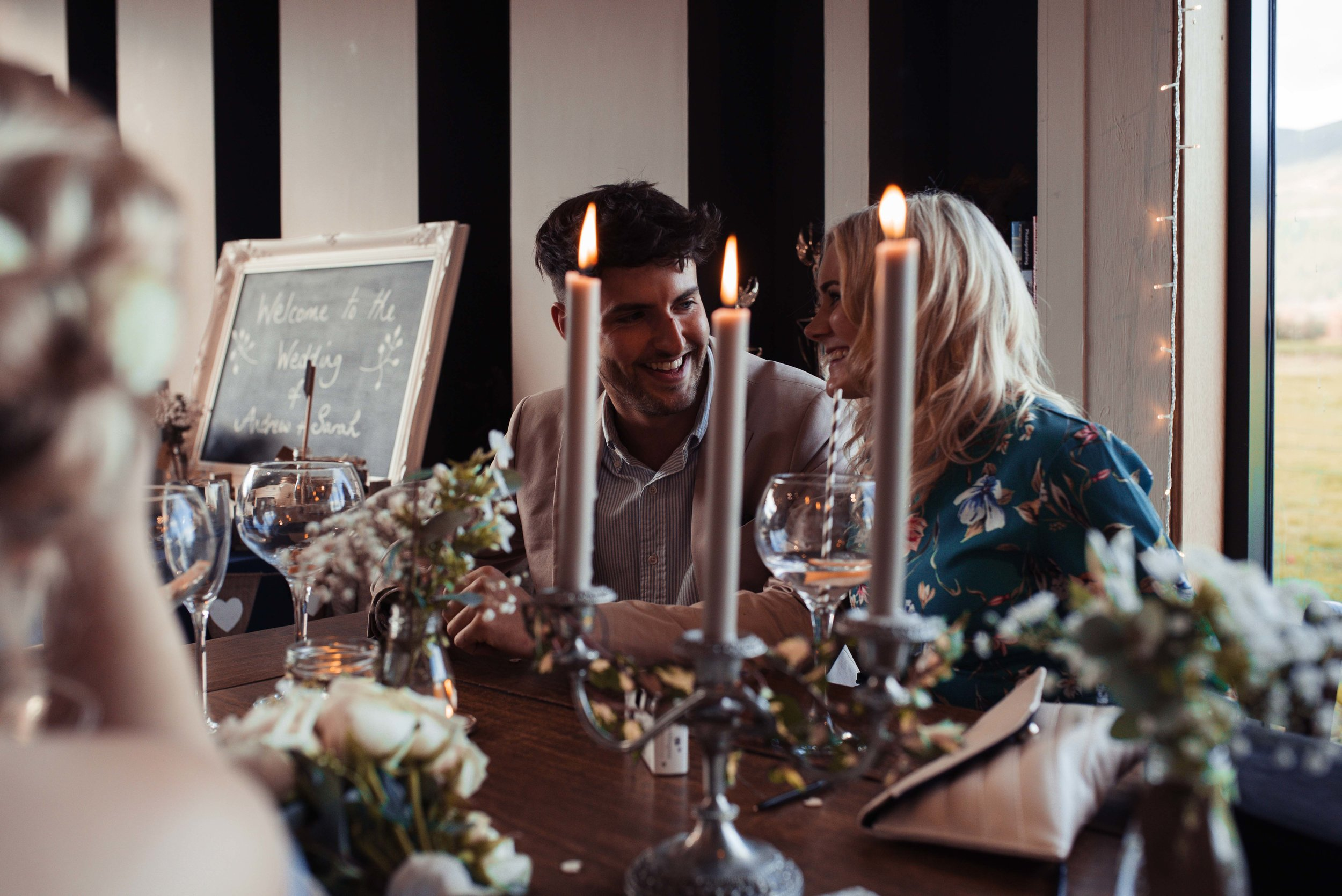 A wedding guest couple sit and have a drink together on a table lit with candles