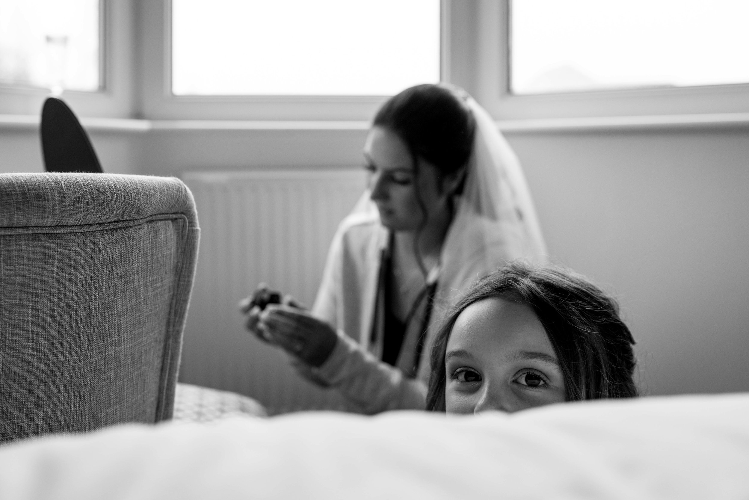 Flower girl pops up from behind the bed while the bride is doing her makeup