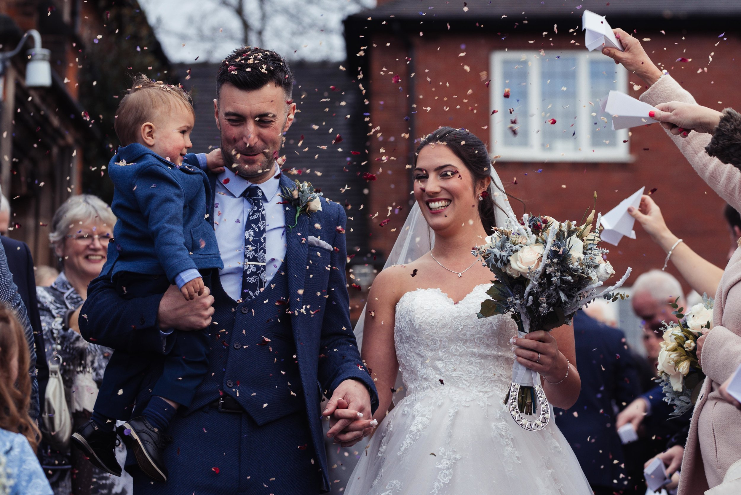 The bride and groom with their son walking through a cloud of confetti