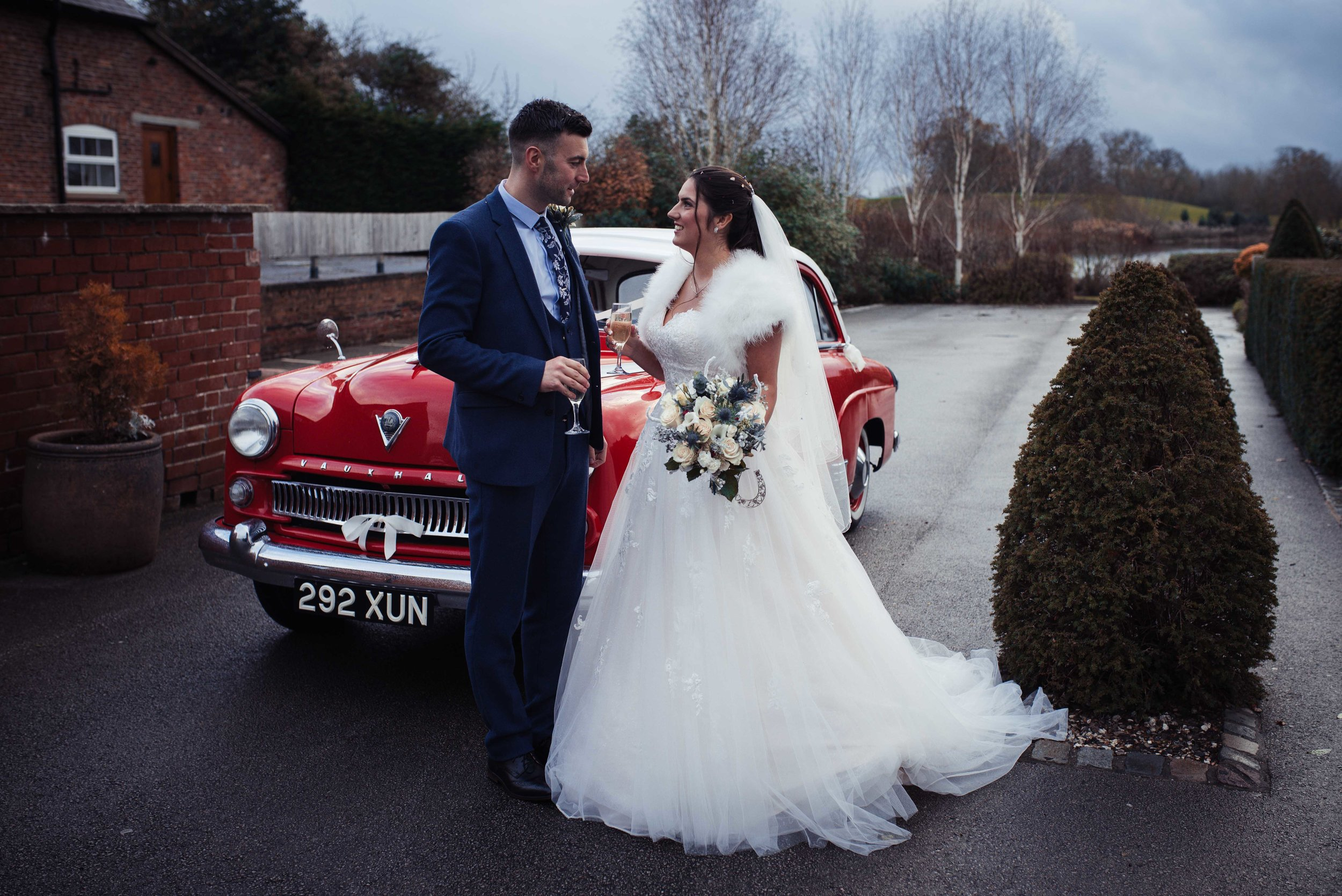 The bride and groom stand in front of their red wedding car with a glass of fizz