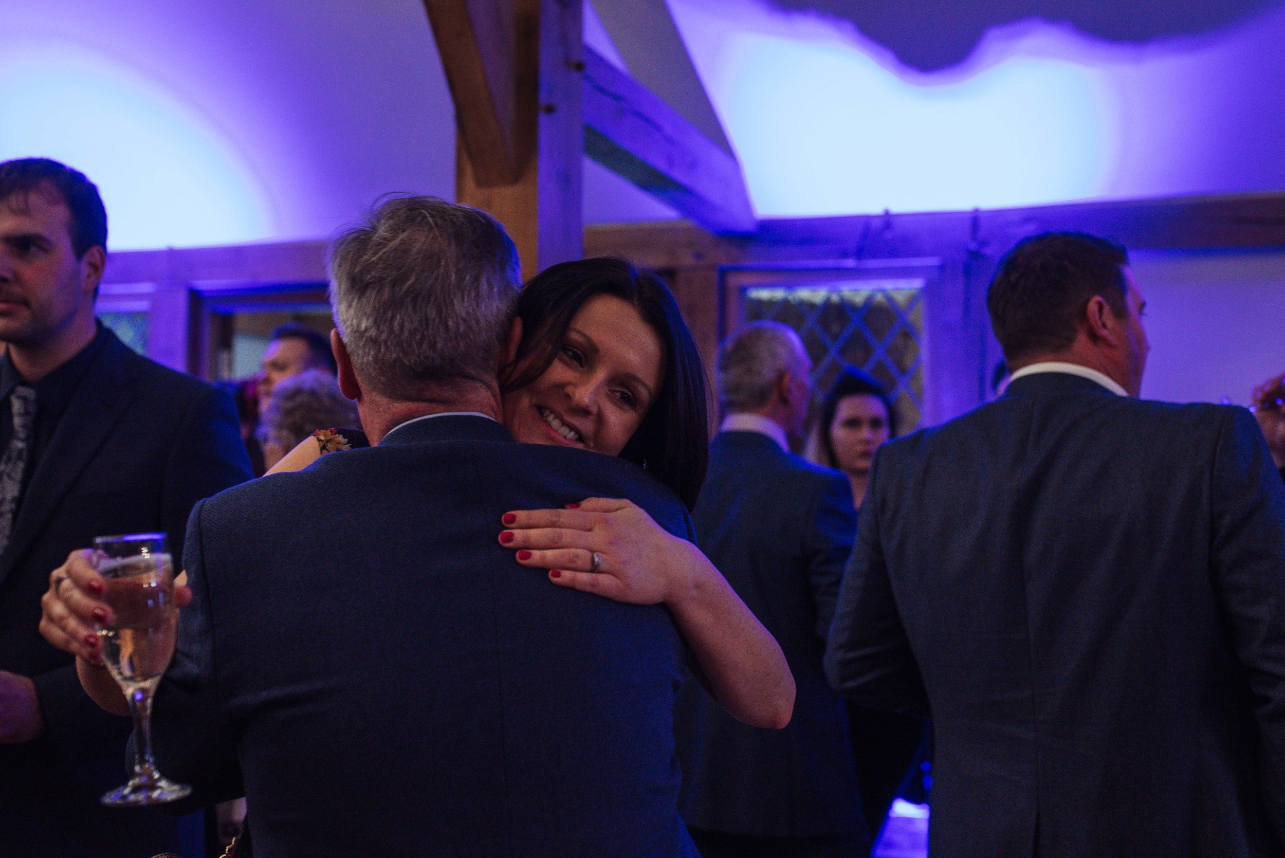 Two wedding guests hug each other