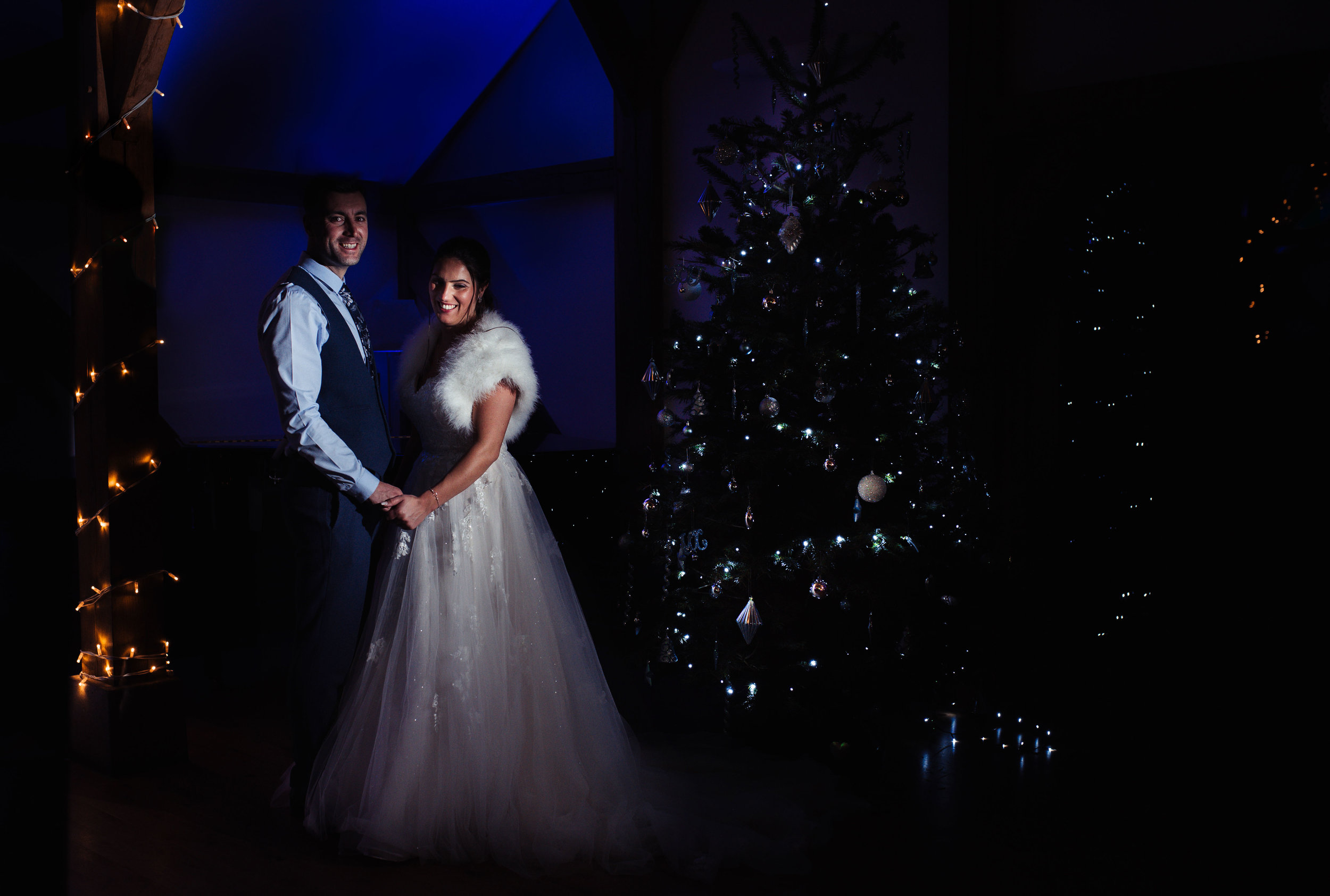 The bride and groom pose in front of the Christmas tree at Sandhole Oak Barn