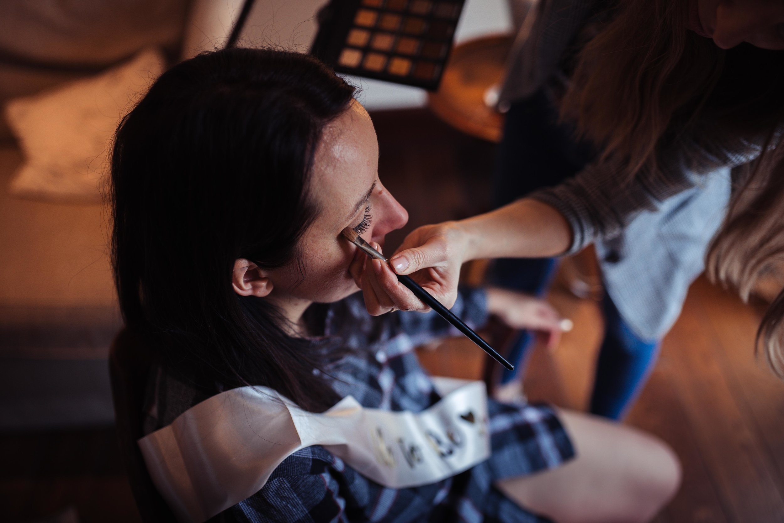 Elevated view of the bride in a blue shirt having her eye makeup applied