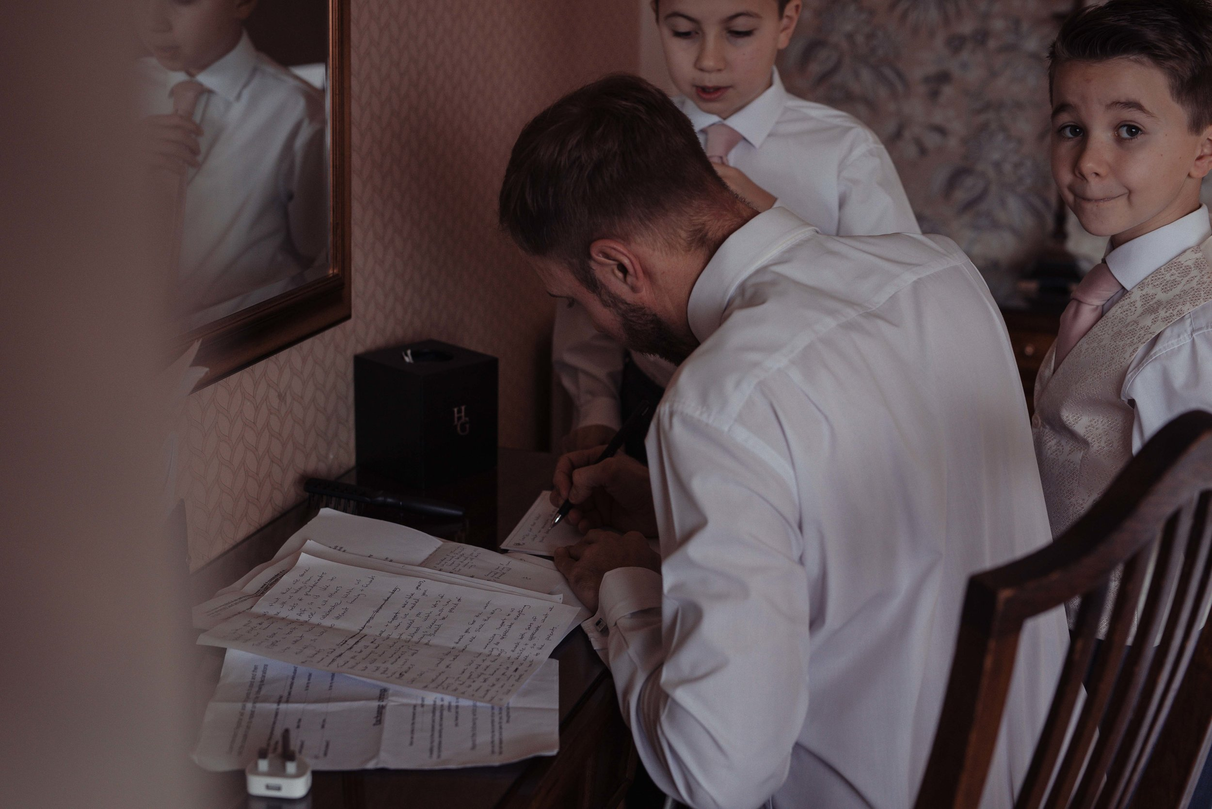 The groom writing his speech a few minutes before the wedding ceremony, with his children watching him