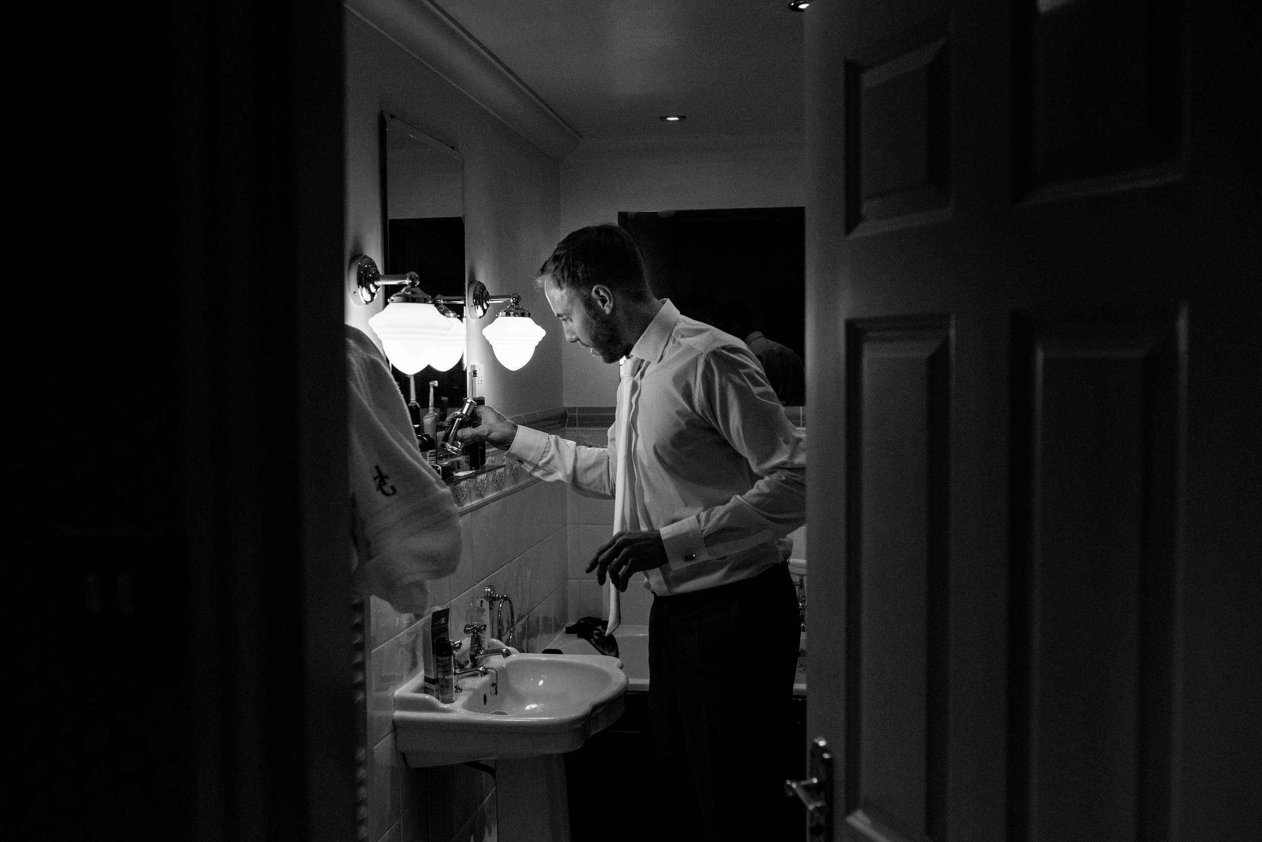 Groom puts on his aftershave in the bathroom of the Holbeck Ghyll
