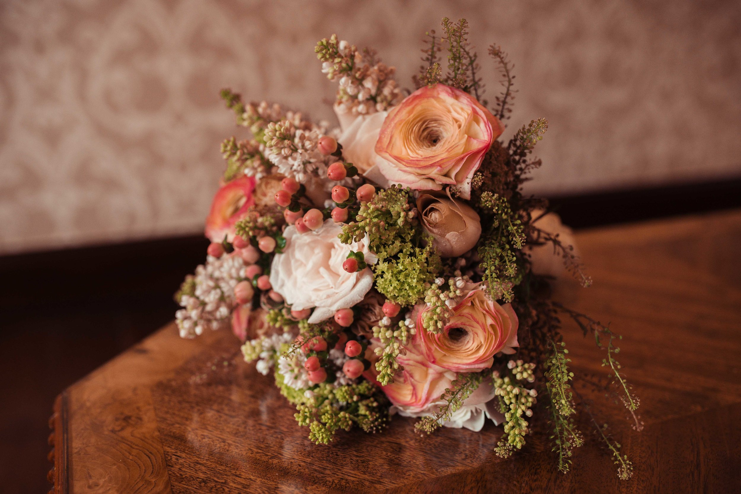 Dusky pink and peach bridal flowers on a table at Holbeck Ghyll