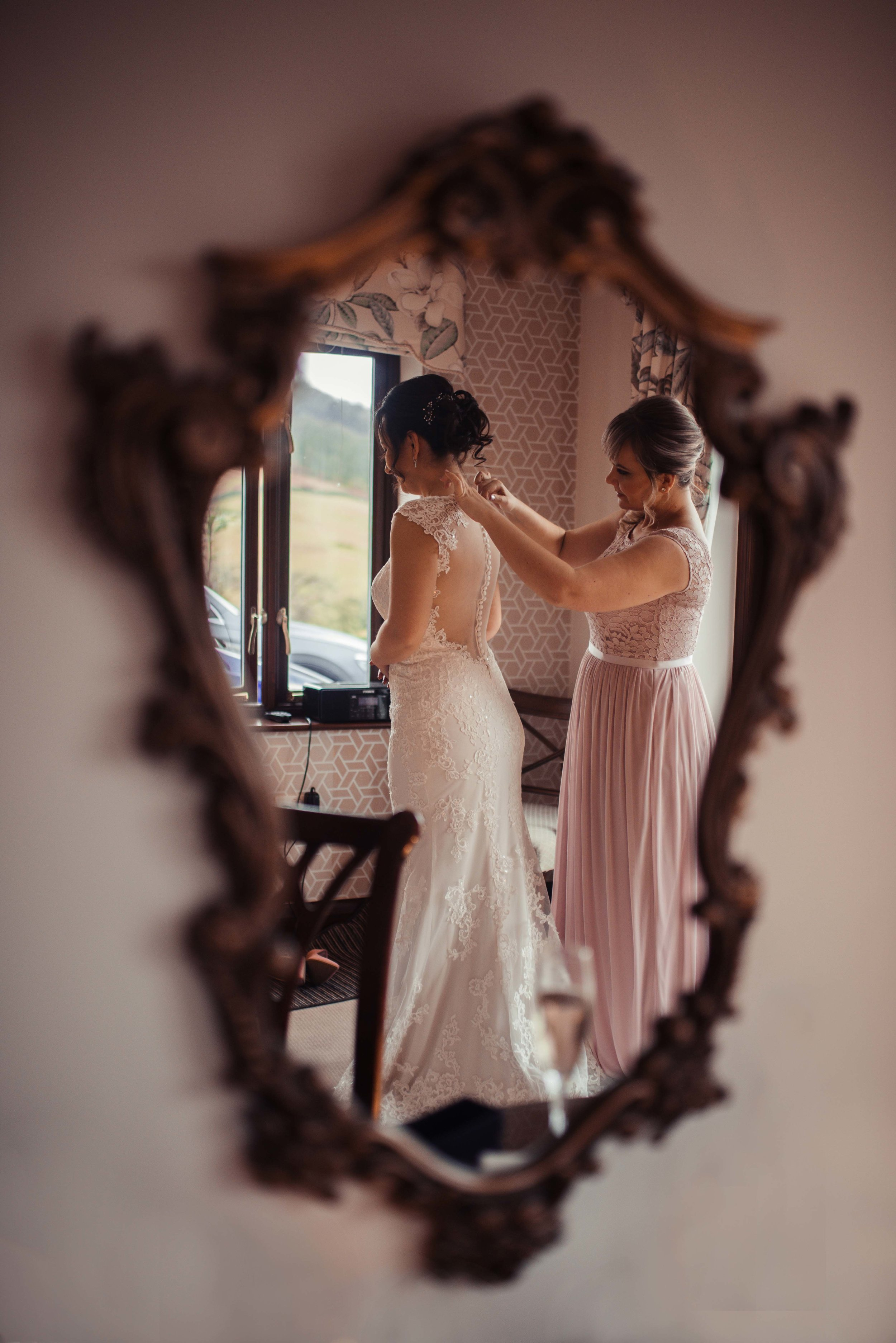 The bridesmaid helping the bride with the final touches of her dress, as seen through a mirror