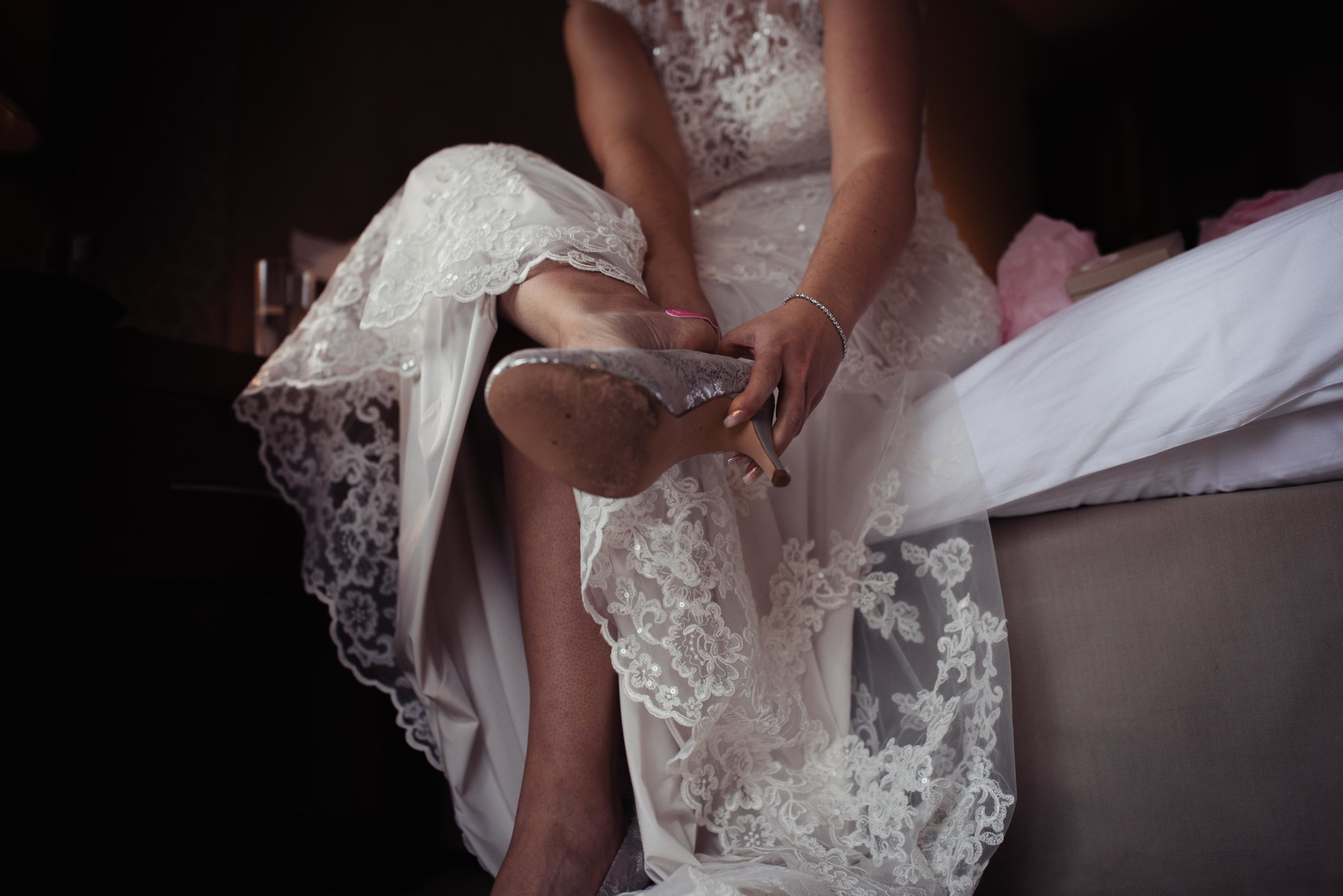 The bride sits on the side of the bed to put her wedding shoes on