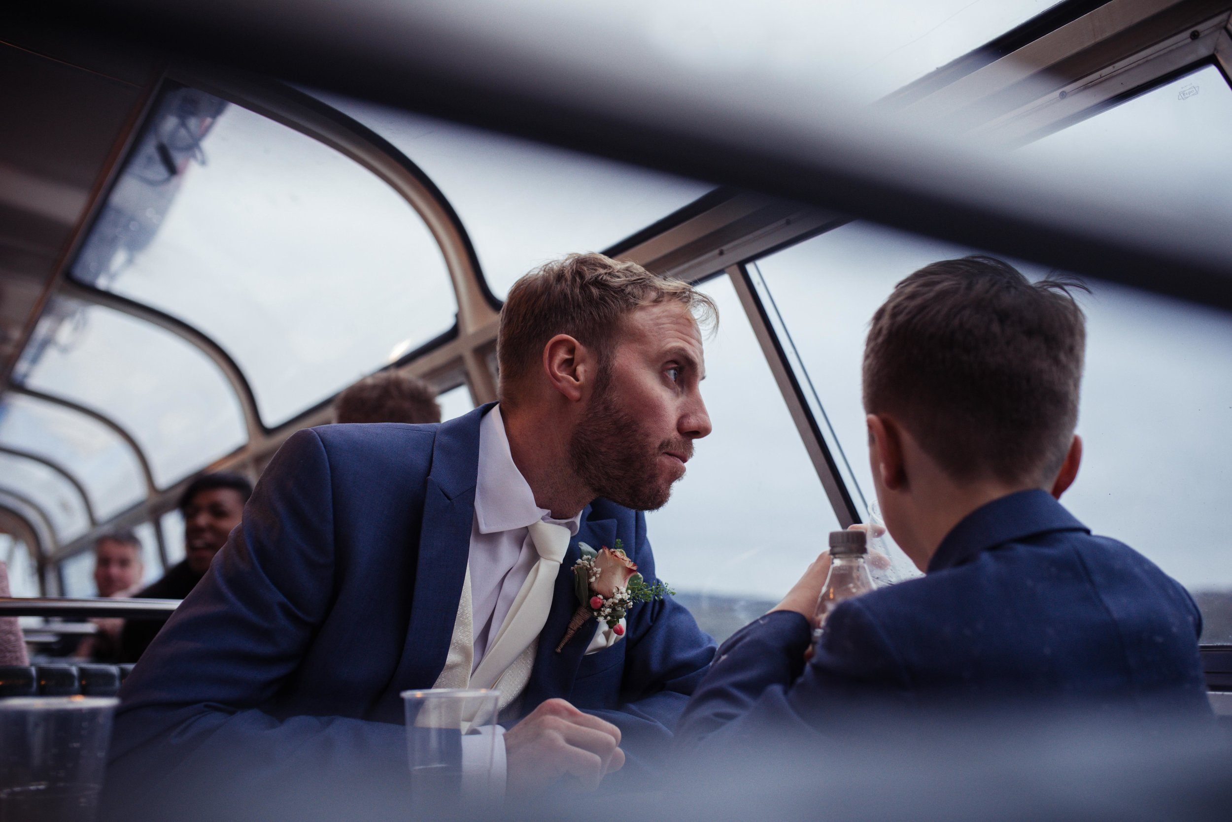 Groom and his son look out of the window of the boat