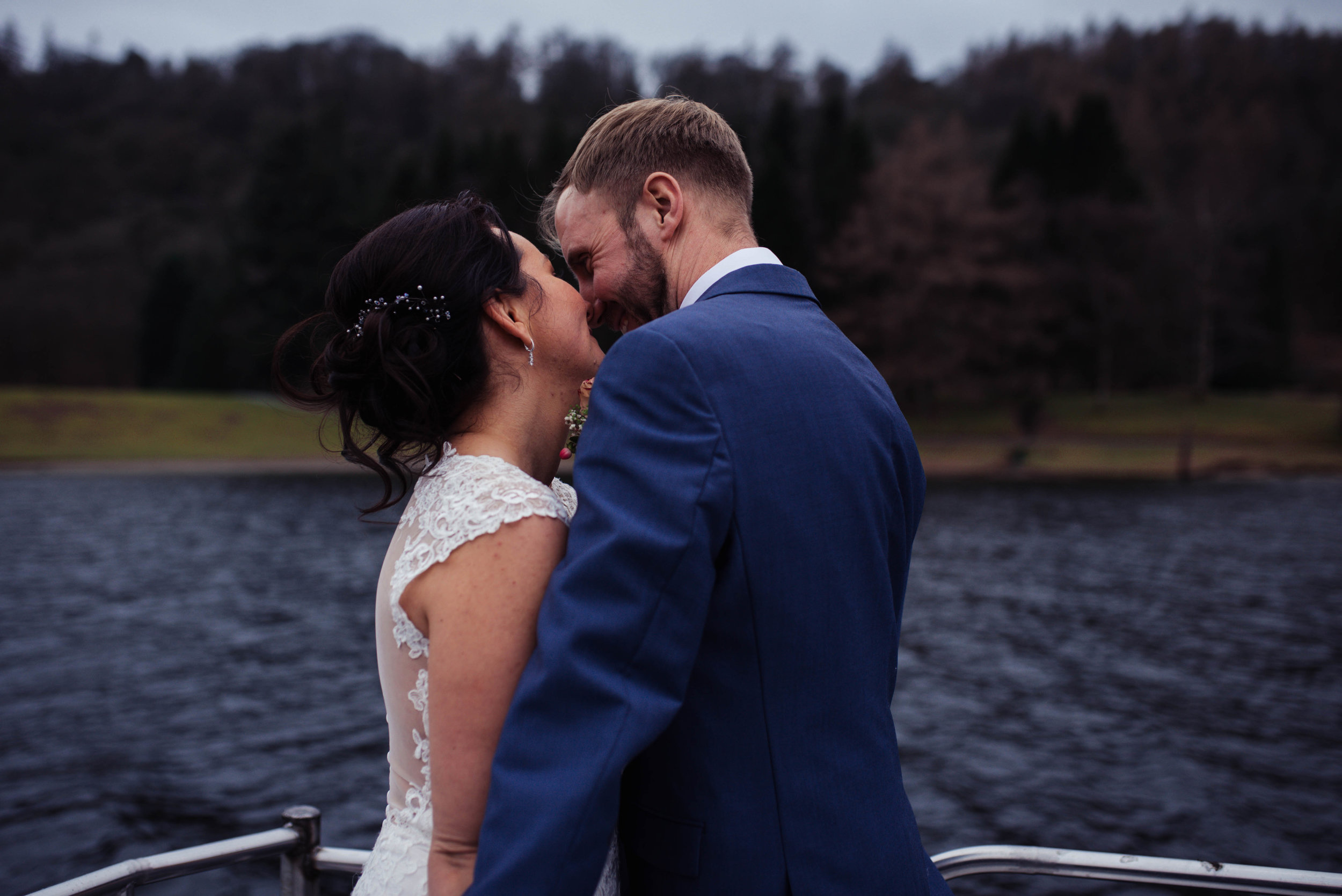 Bride and groom share a kiss facing away from the camera towards the lake