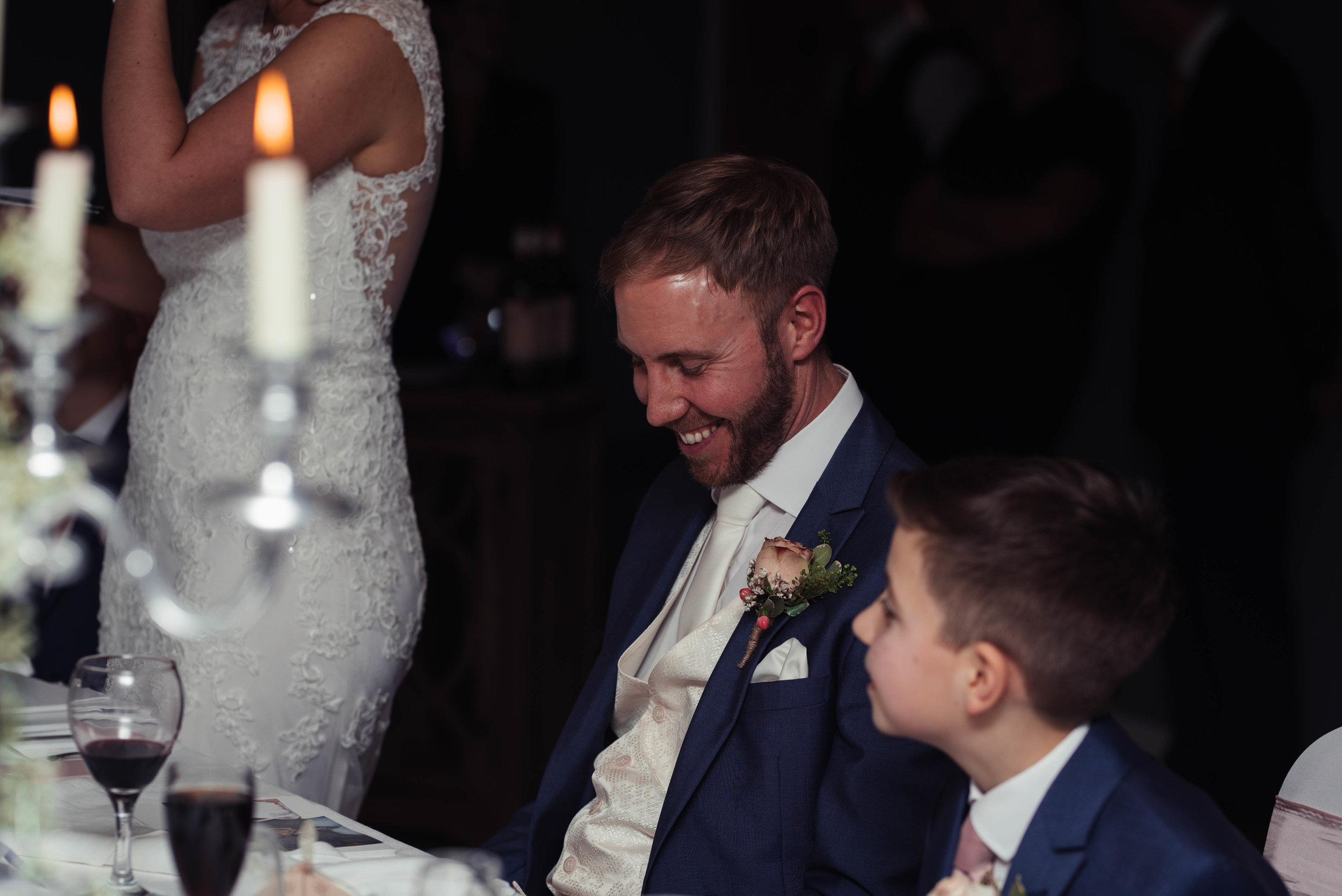 The groom sits with his son while his bride delivers her speech
