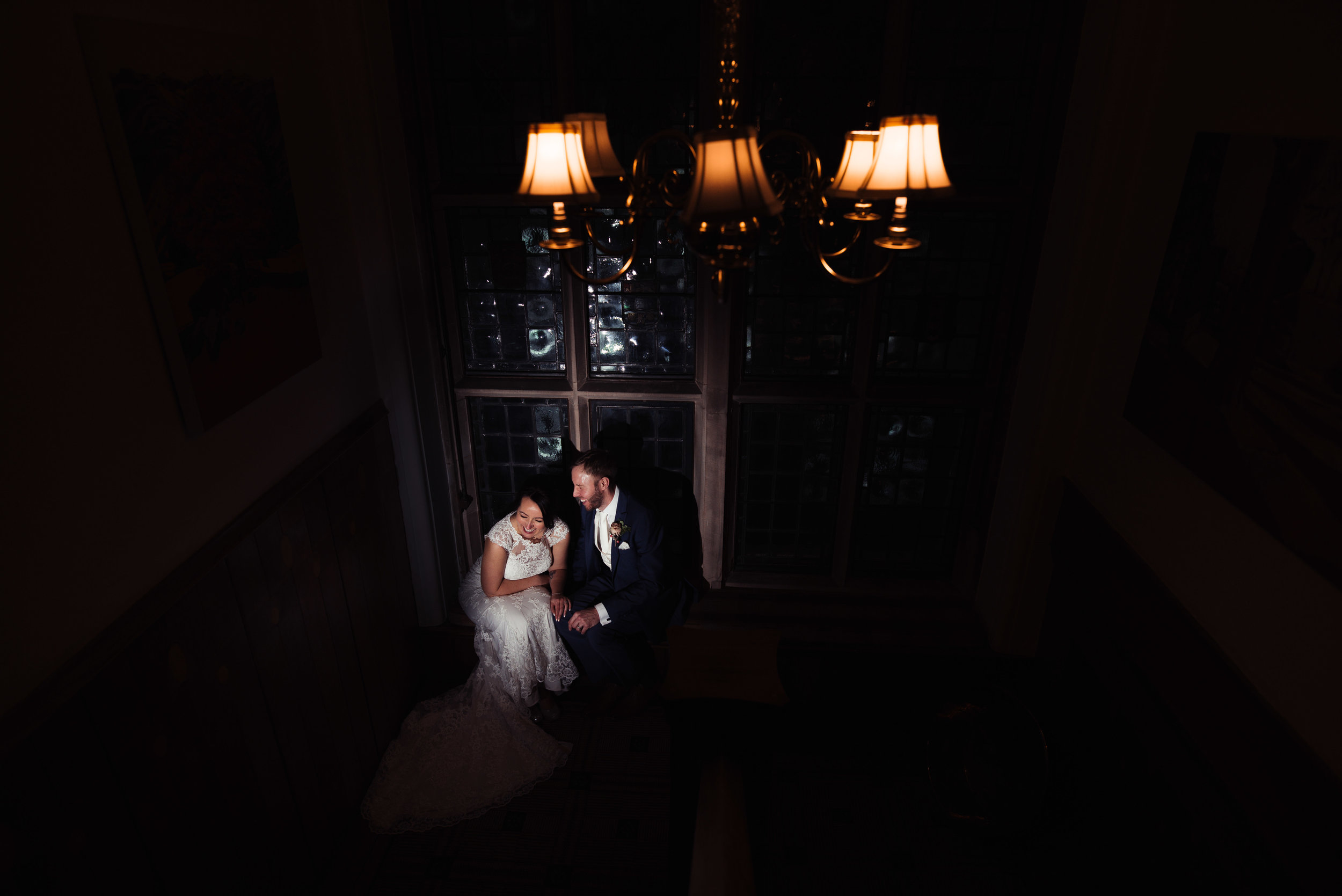 Bride and groom share a laugh together on the stairs during their wedding photography session