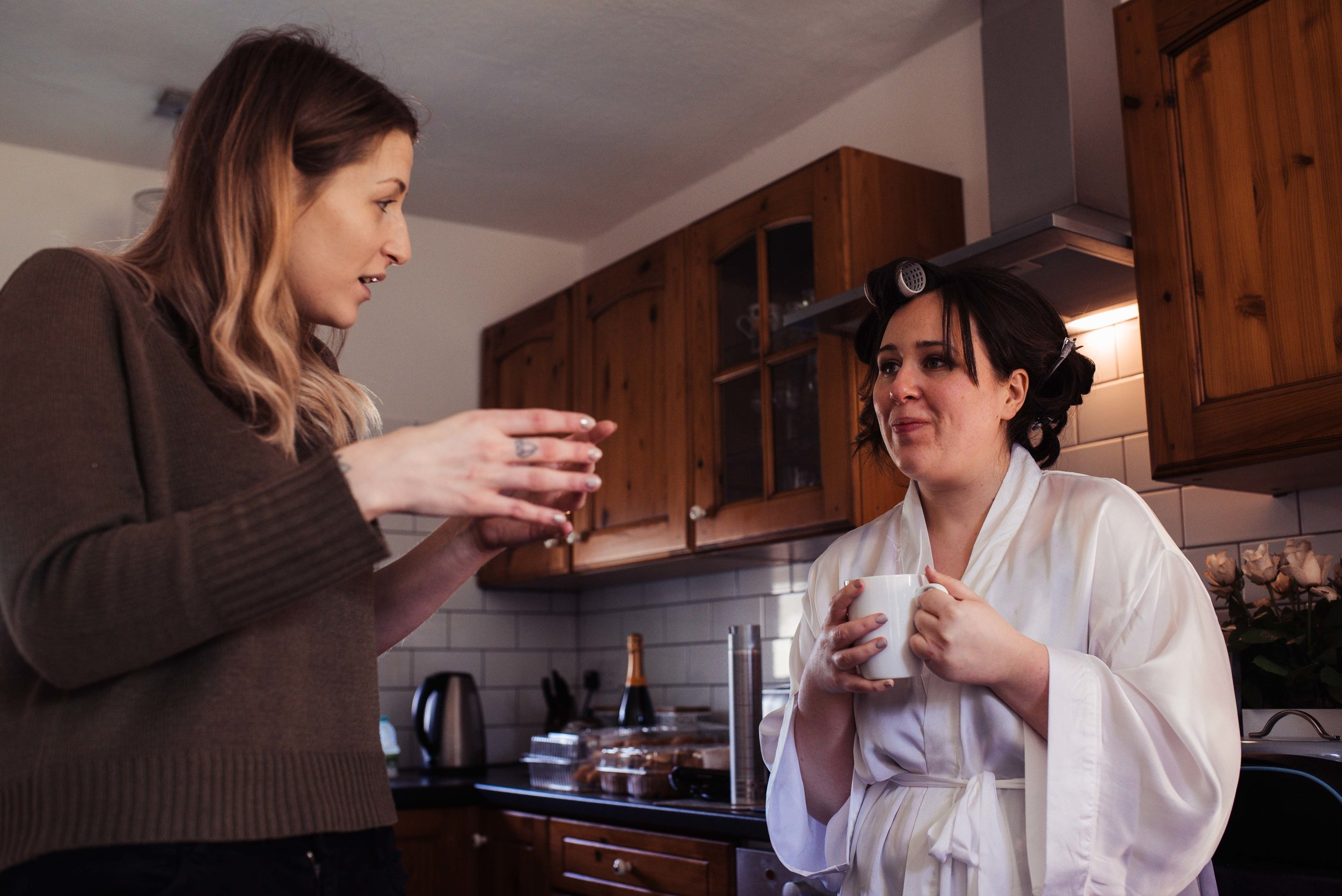 Bride chatting to her maid of honour over a cup of tea