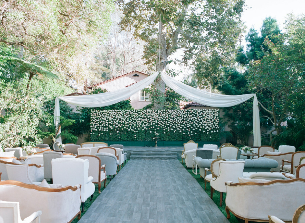 Elegant wedding ceremony with mismatched love seats, vintage chairs, and couches for a comfortable and unique ceremony seating setup.