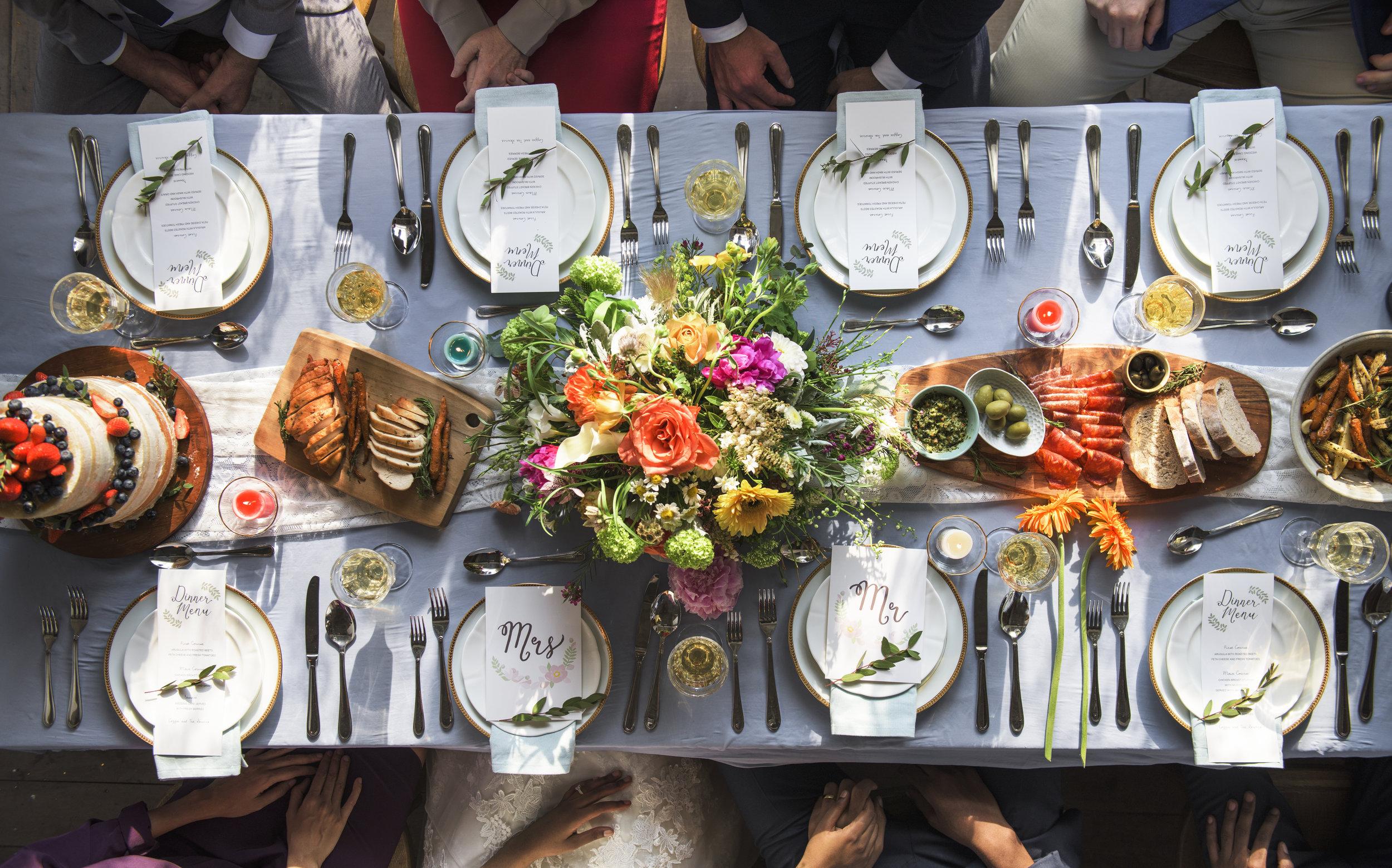 A long reception table at an outdoor wedding.