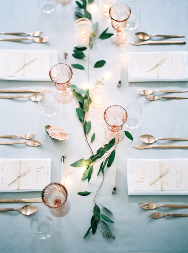 A minimalist tablescape with rose glassware, rose gold flatware and a touch of greenery.