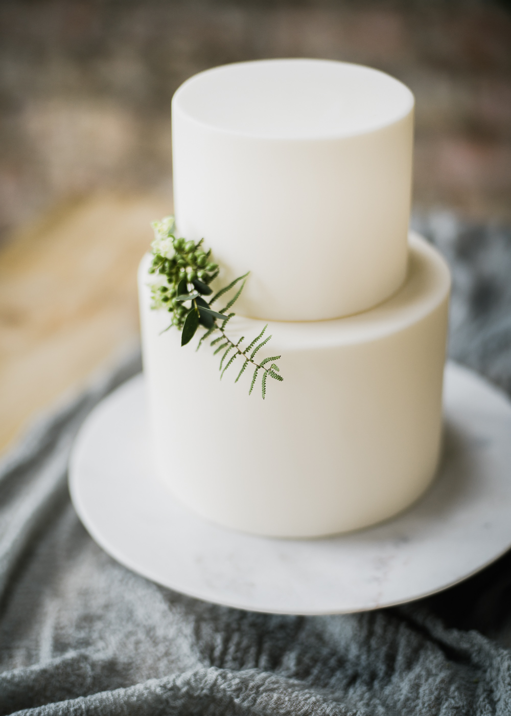 An elegant white wedding cake adorned with foliage.