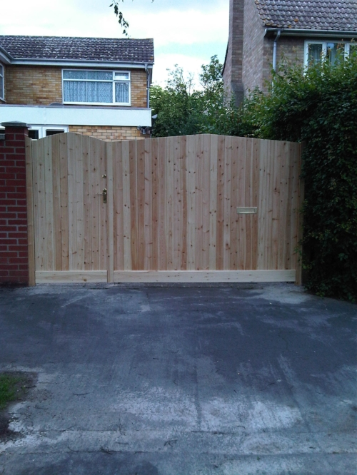 - GatesA wooden gate for a driveWe have experience of making, supplying and fitting both single and double gates. One job that comes to mind was for a customer who needed a set of gates to span a 4-metre wide driveway. Their initial idea was for two wooden gates of equal size, 2 metres high by 2 metres wide. We realised, however, that gates of this size would not only be very heavy to open and close all the time, but would also twist significantly, being made out of a natural material. In consultation with the customer, we decided to make the gates of equal height but unequal width, to end up with one small, light gate and one large, heavy one: the former to be used on a daily basis, for easy pedestrian access in and out of the driveway, and the latter to be used on the rare occasions when the customer needed to drive the car in or out.