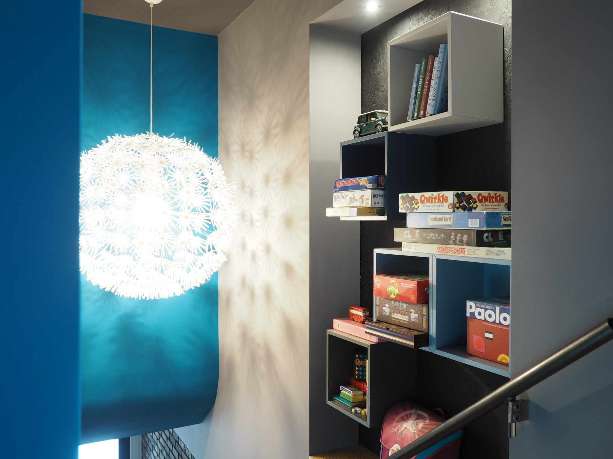 In this niche along a staircase I provided for shelving to hold board games, books, and toys. Easily reached as you climb the steps, enriching the staircase and giving thinkness to a feture wall in the home.