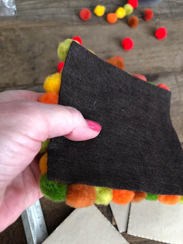 felt backing of hand made pom-pom coaster