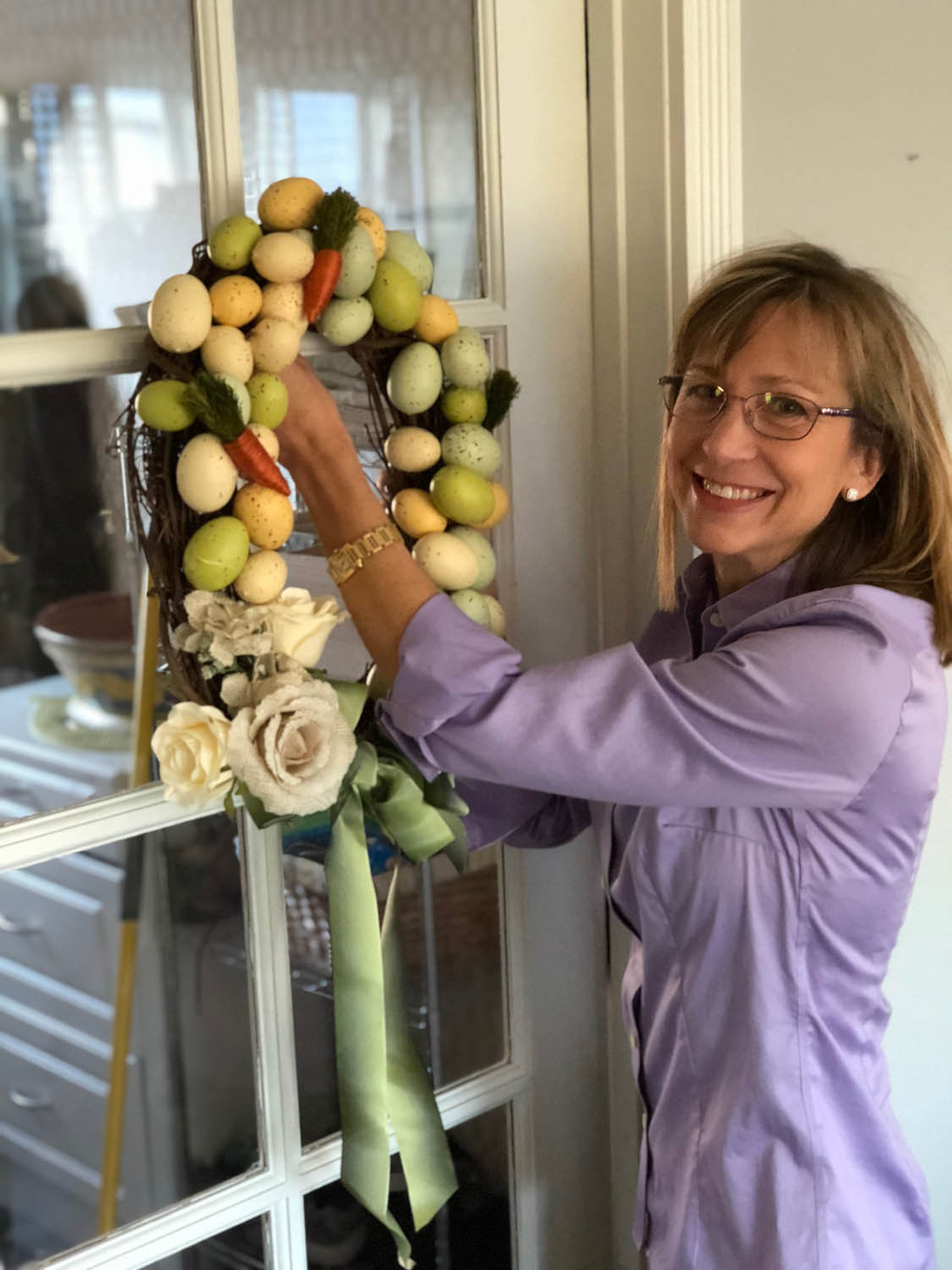 Ashley hangs up the hand made Easter egg wreath on a paned glass door