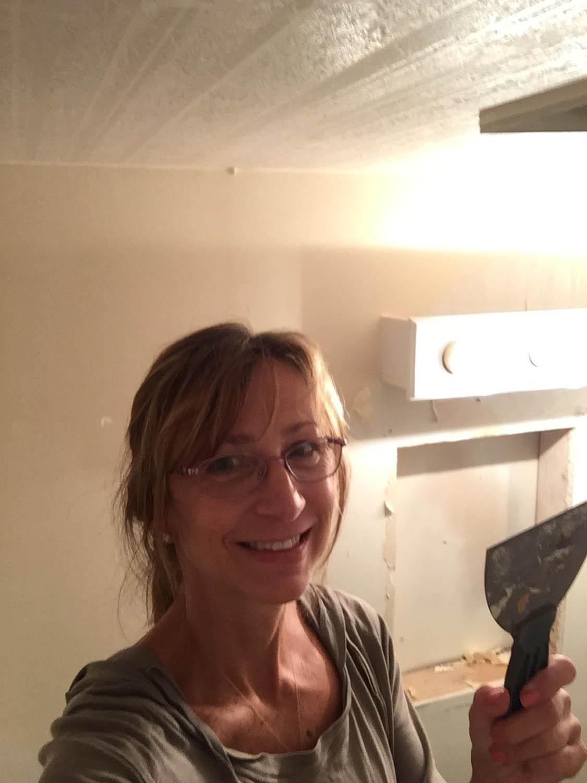 Ashley removing wallpaper with a scraper
