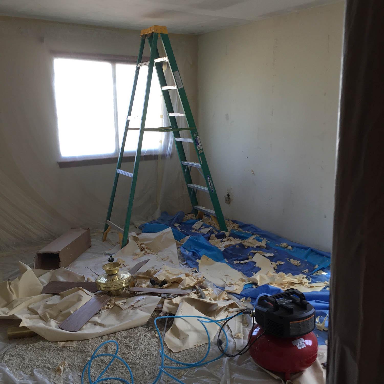 ladder in bedroom during wallpaper removal