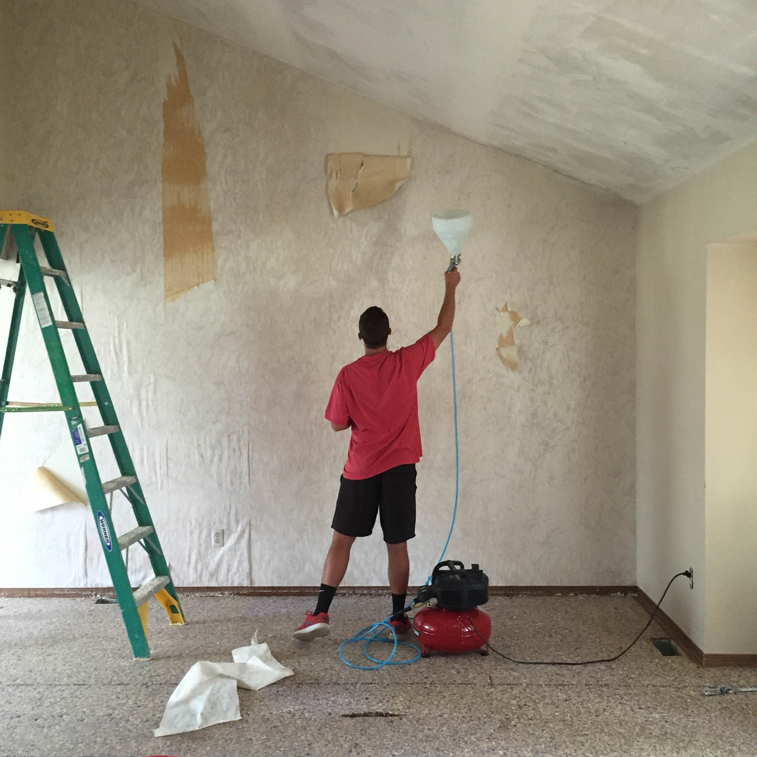worker removing wallpaper in the living room