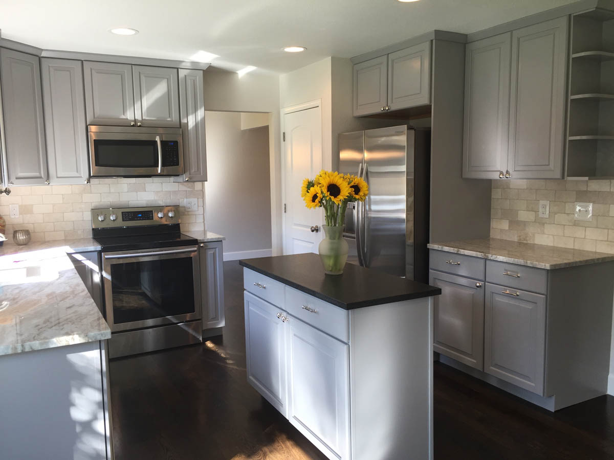 kitchen with grey cabinets and stainless refrigerator after