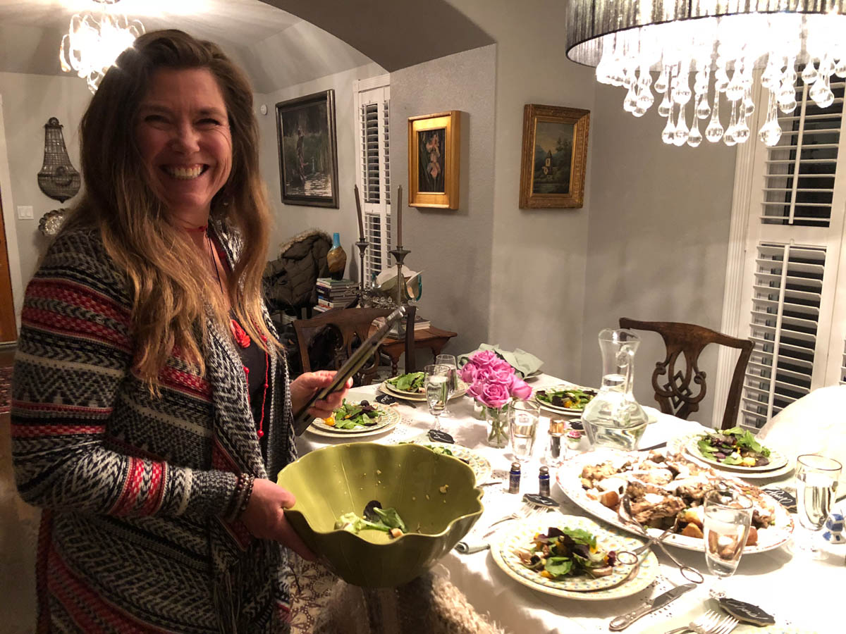 Hillary serving salad at the table