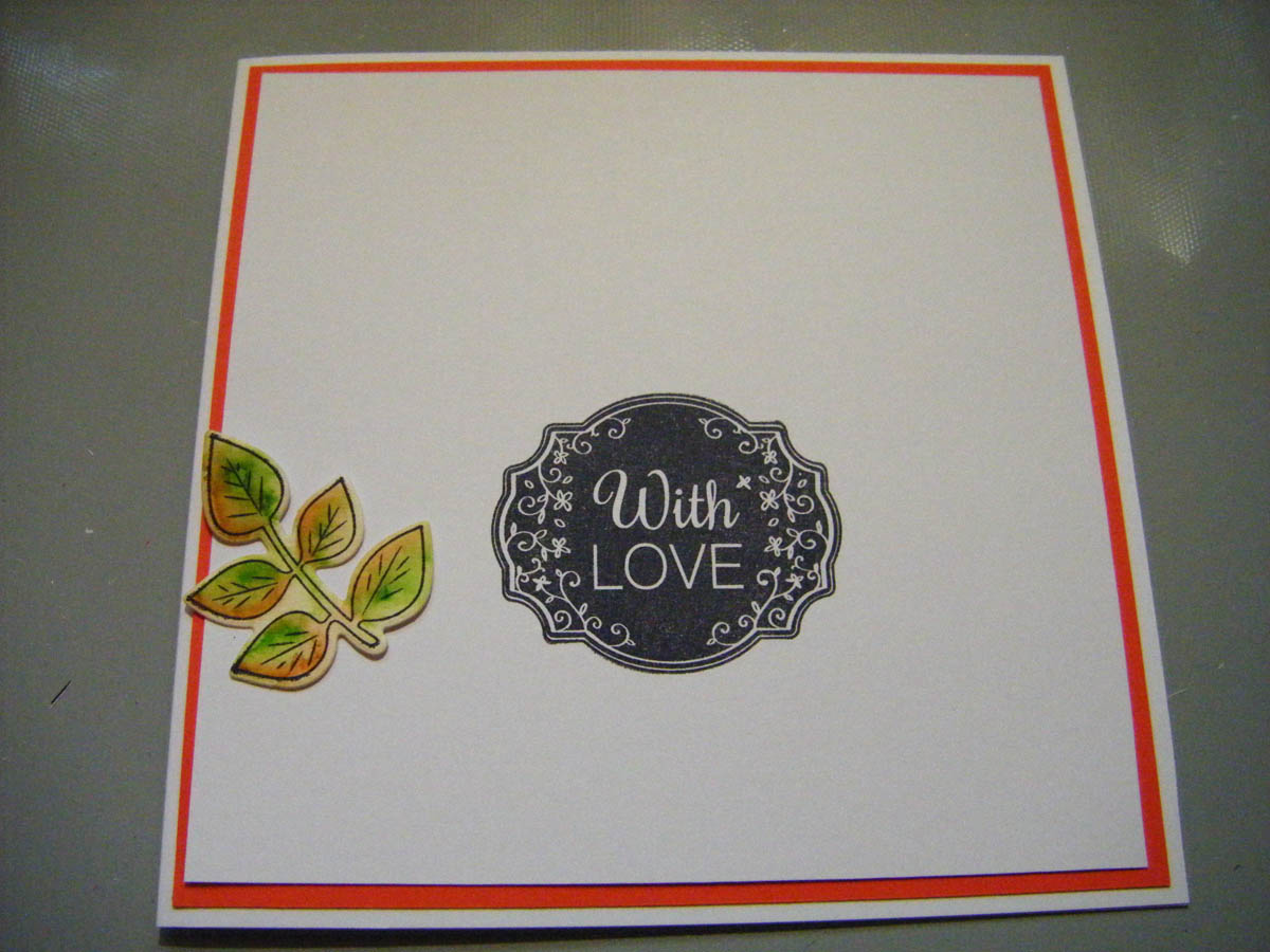 Begin gluing die-cut greenery shapes around the sentiment