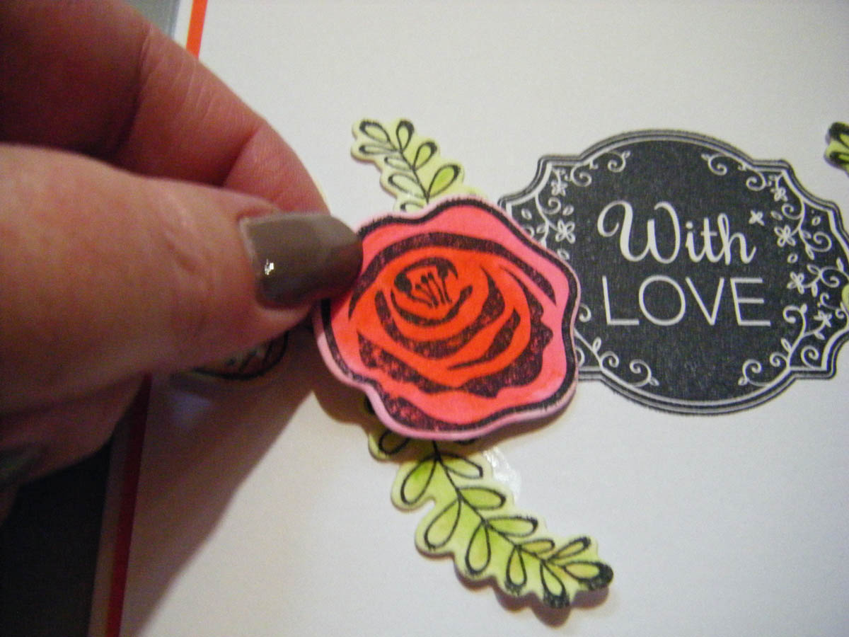 Begin adding larger floral die-cut shapes to the card