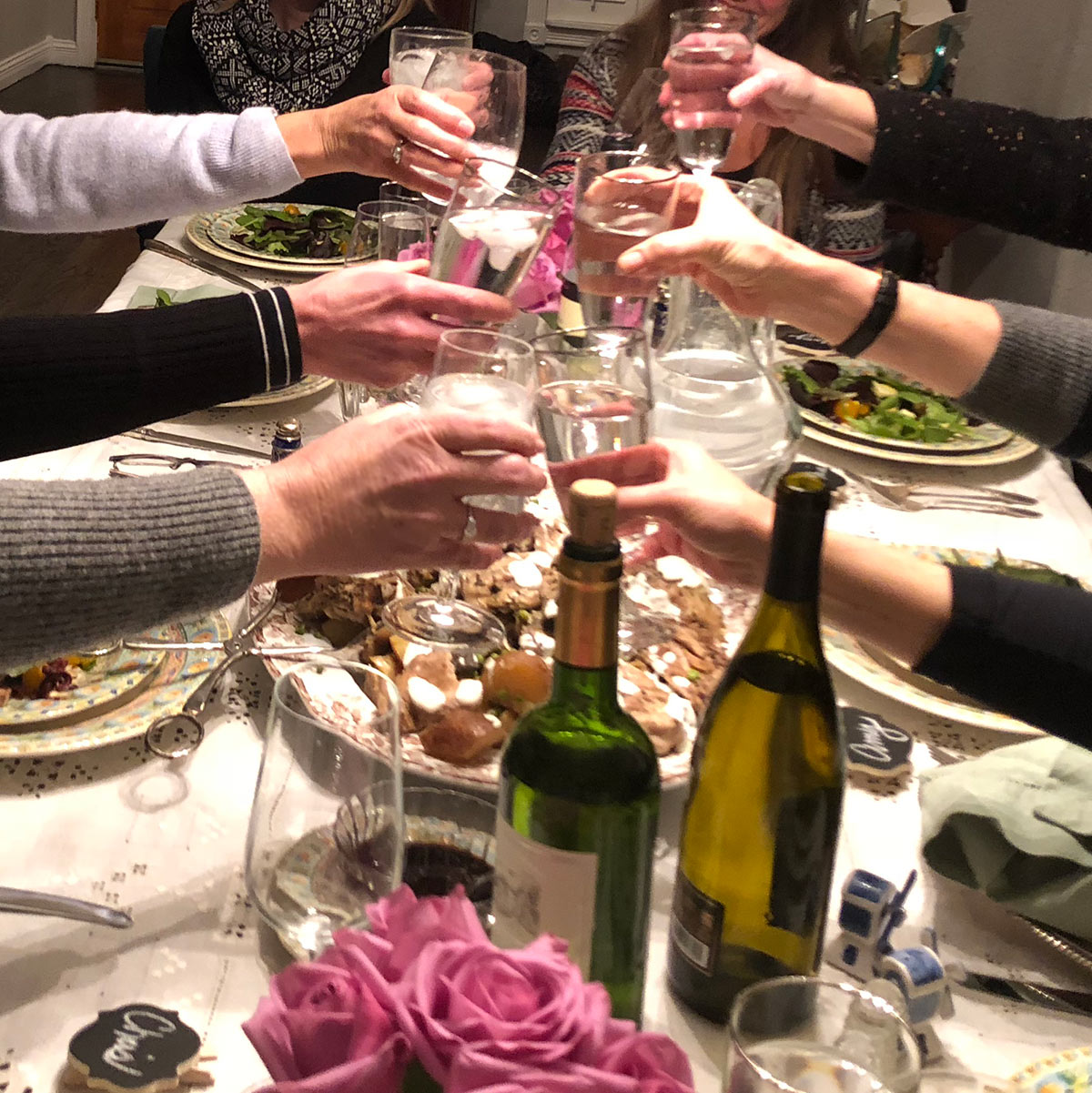 Book club ladies toasting with wine at dinner