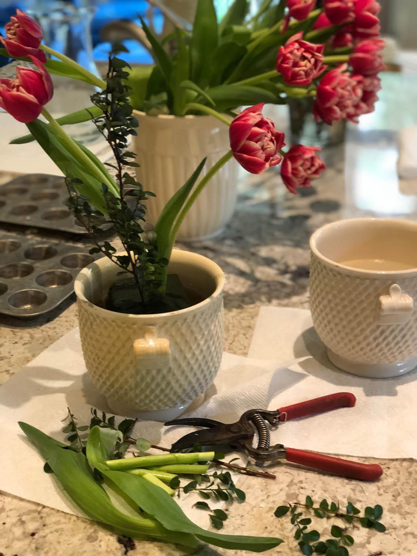 Arranging tulip and boxwood in ceramic vessel
