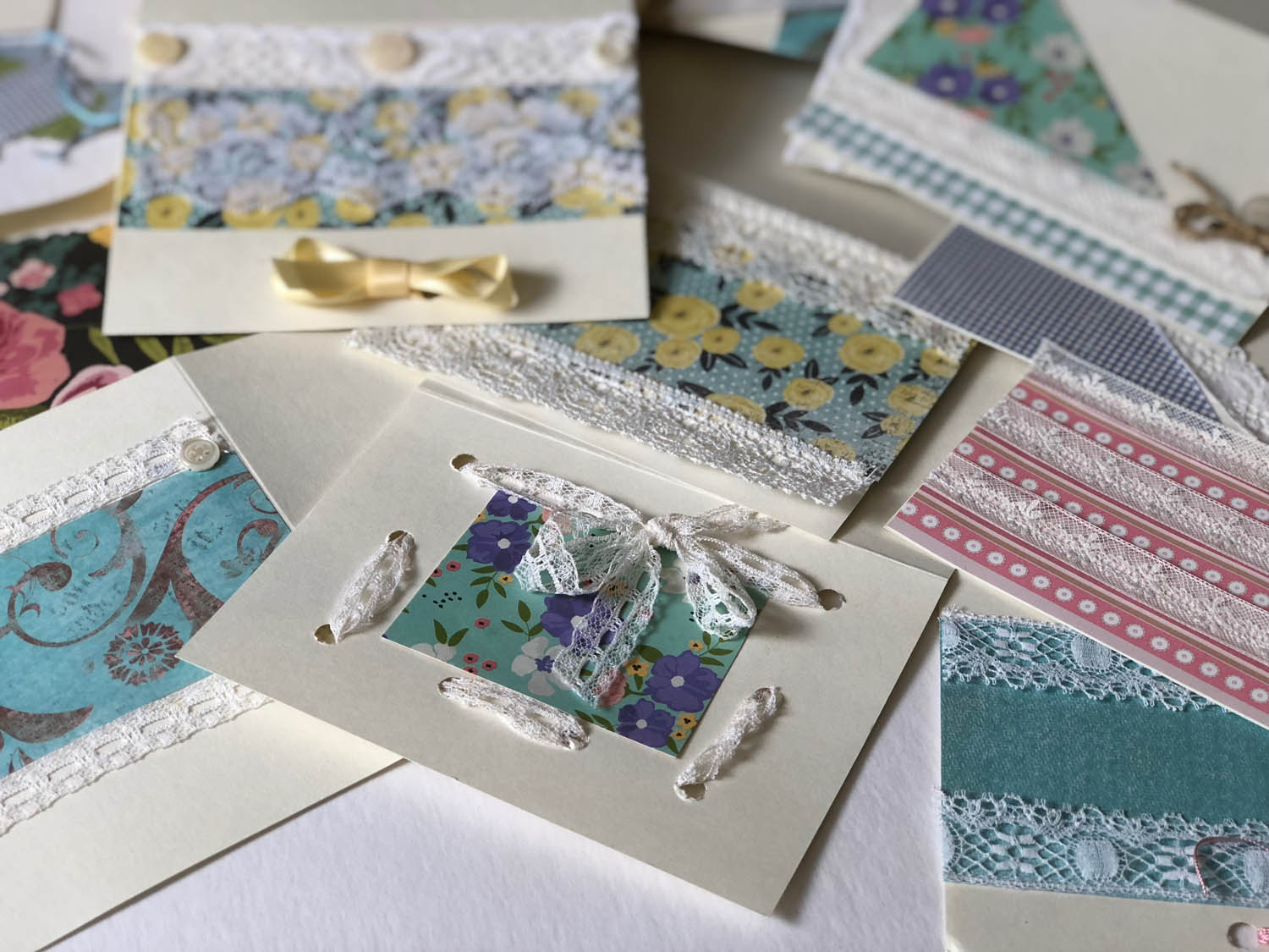 assortment of handmade cards with vintage lace and fabrics