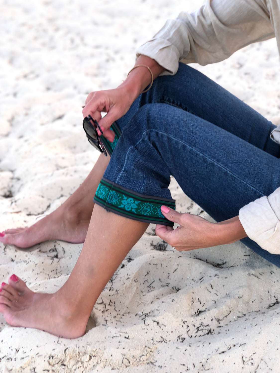 sitting on beach in embellished jeans
