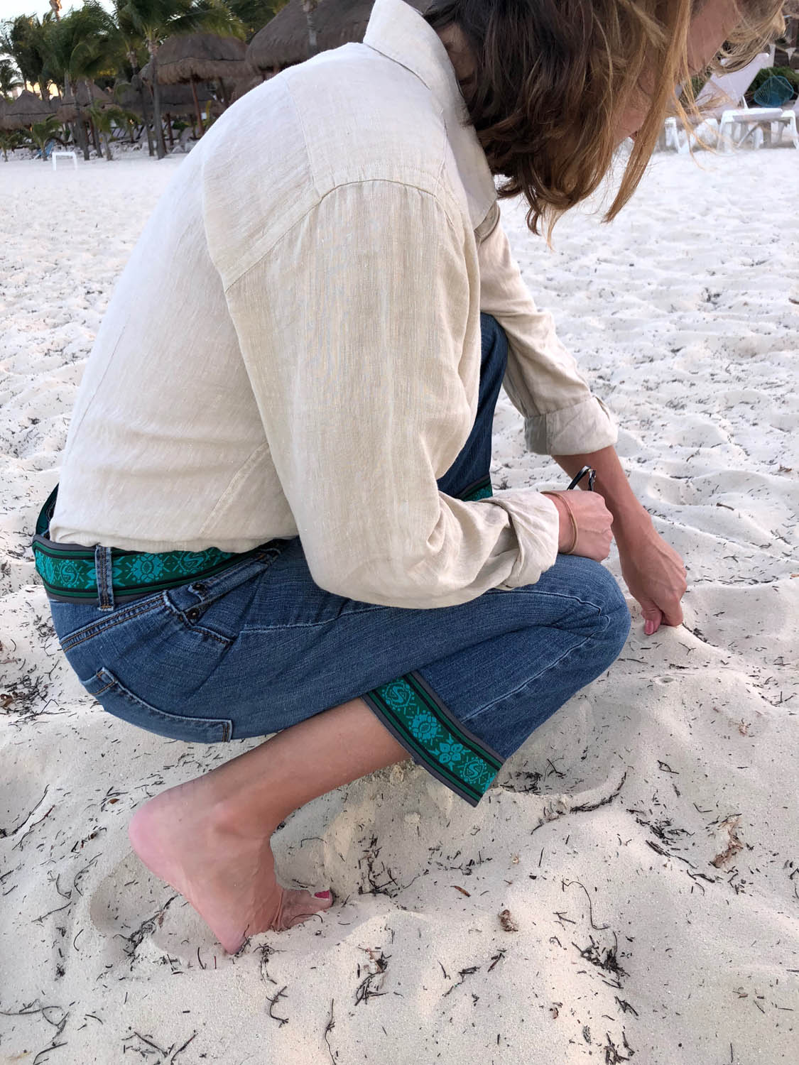 kneeling in the sand with embellished jeans