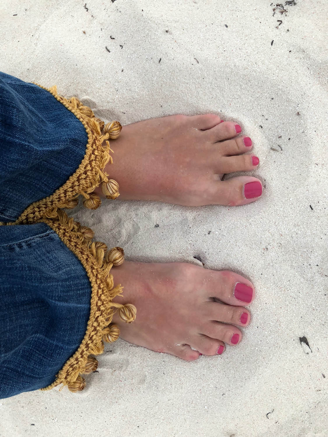 standing in sand with gold trim embellished denim blue jeans