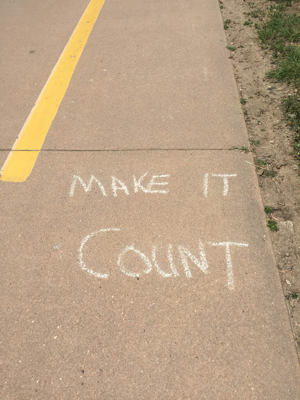 Make It Count hand written chalk message on bike path