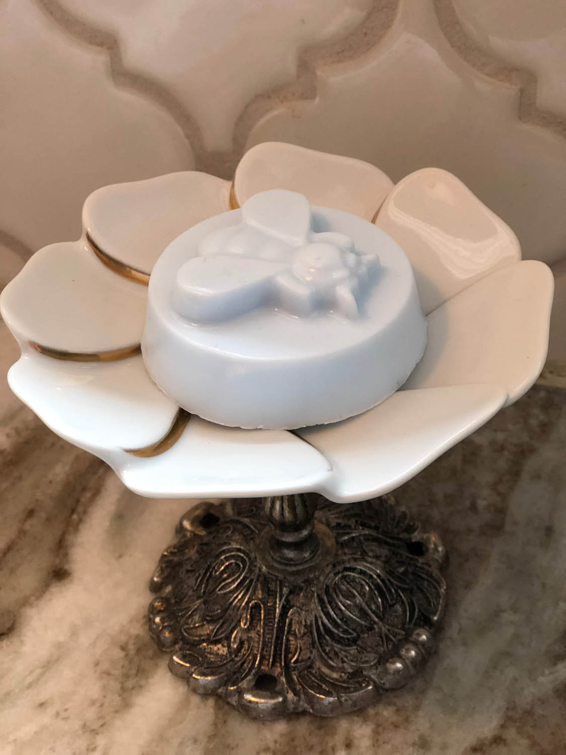 closeup of small bee goat milk soap in soapdish