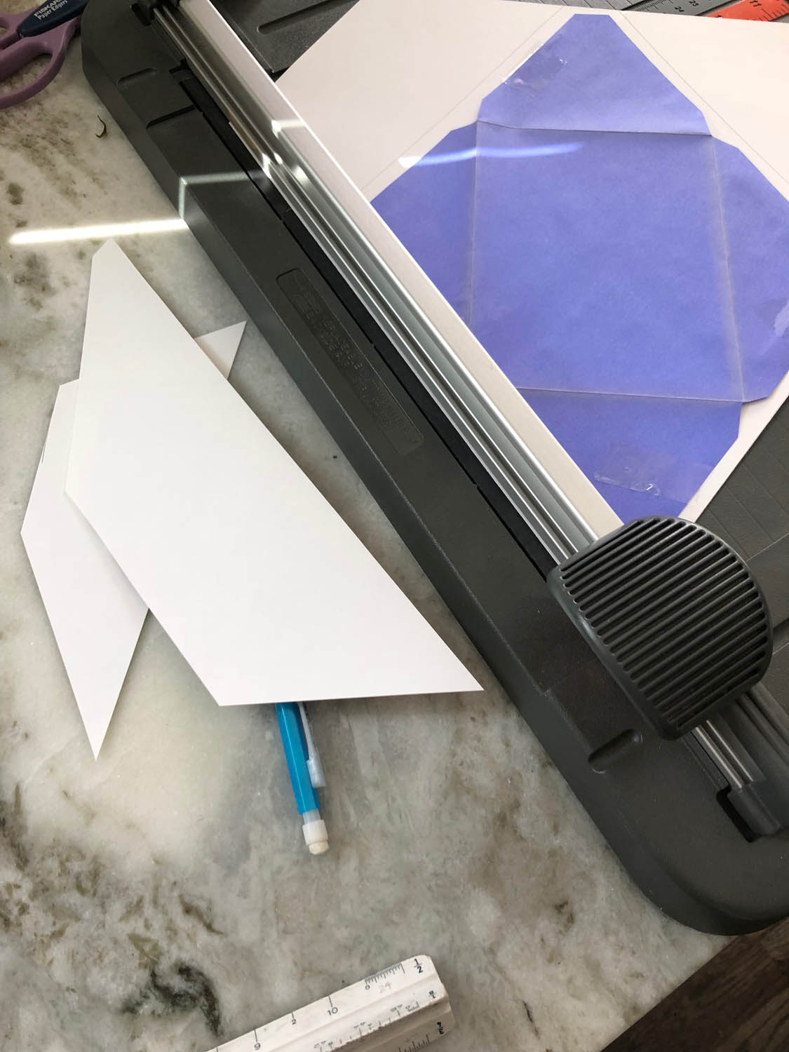 trimming white card stock for DIY envelopes with scrapbook paper