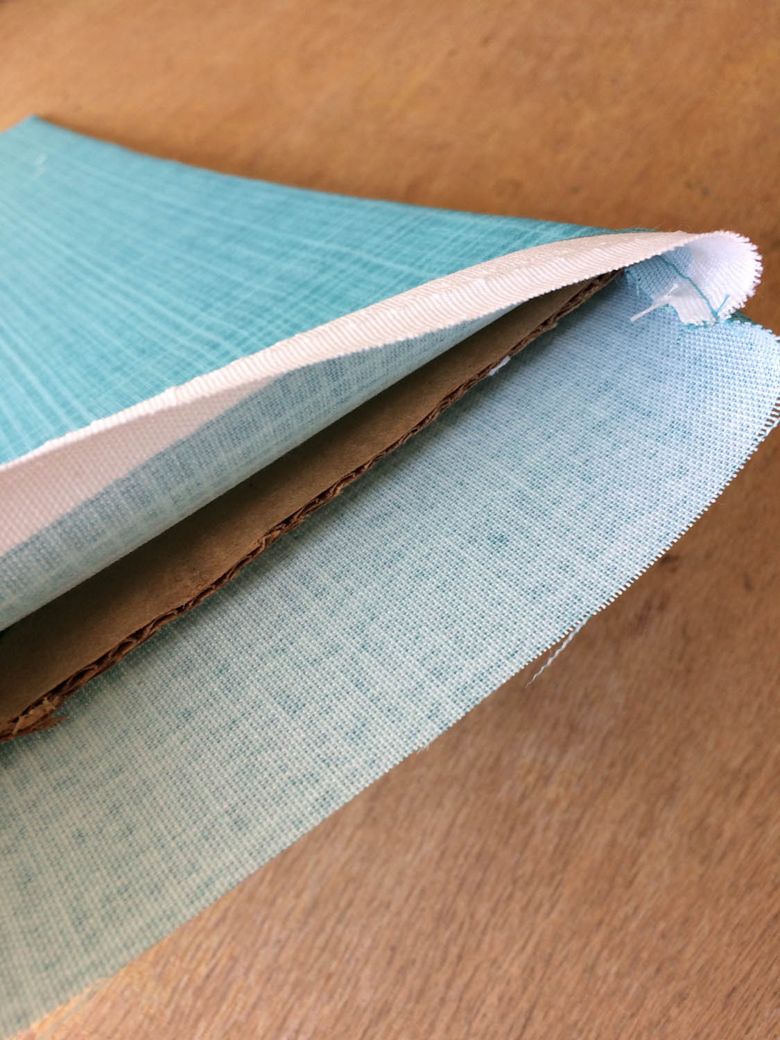 inserting cardboard base into fabric cover