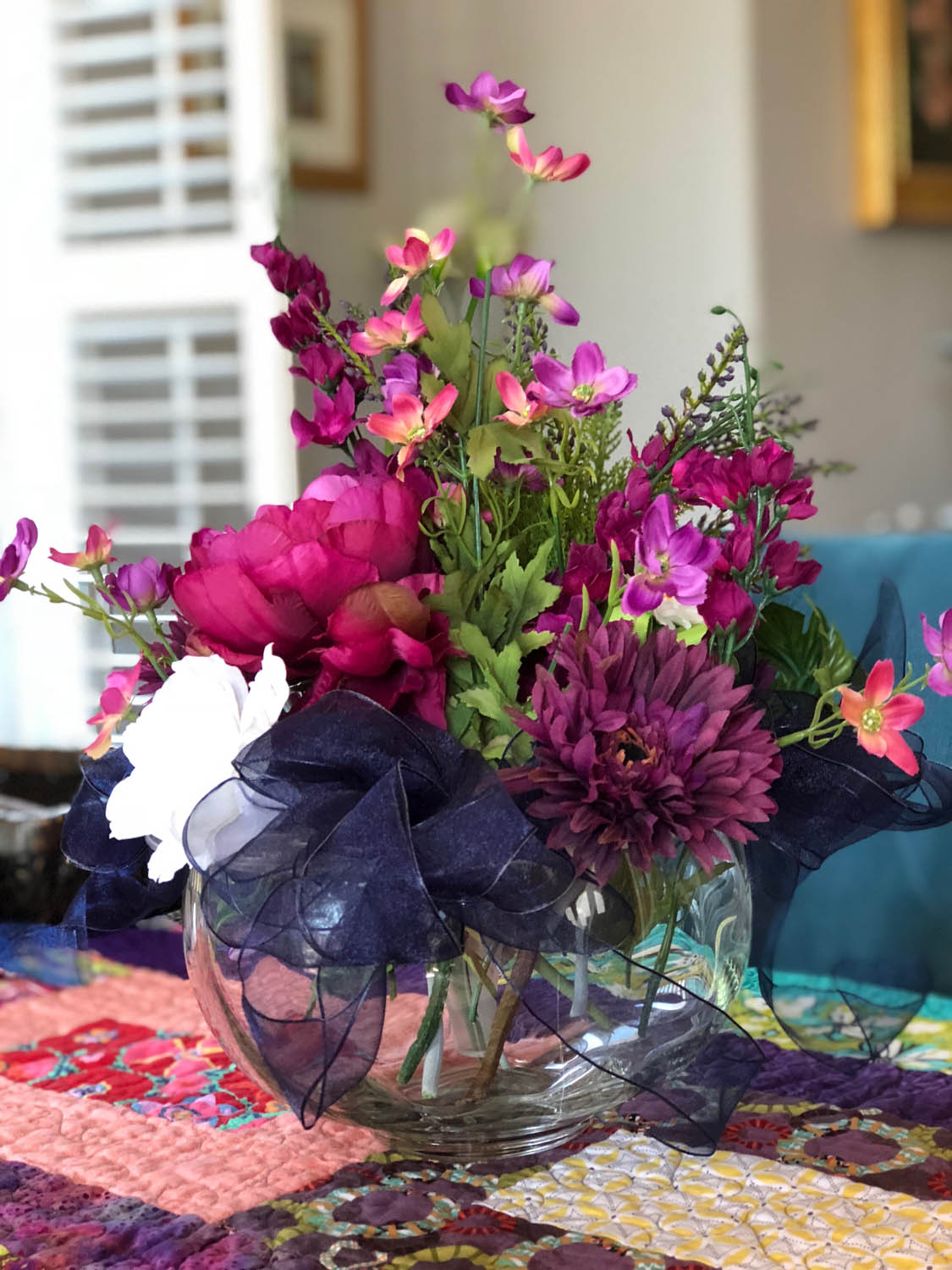 Simple centerpiece arrangements with flowers, ribbons and a Bow K base
