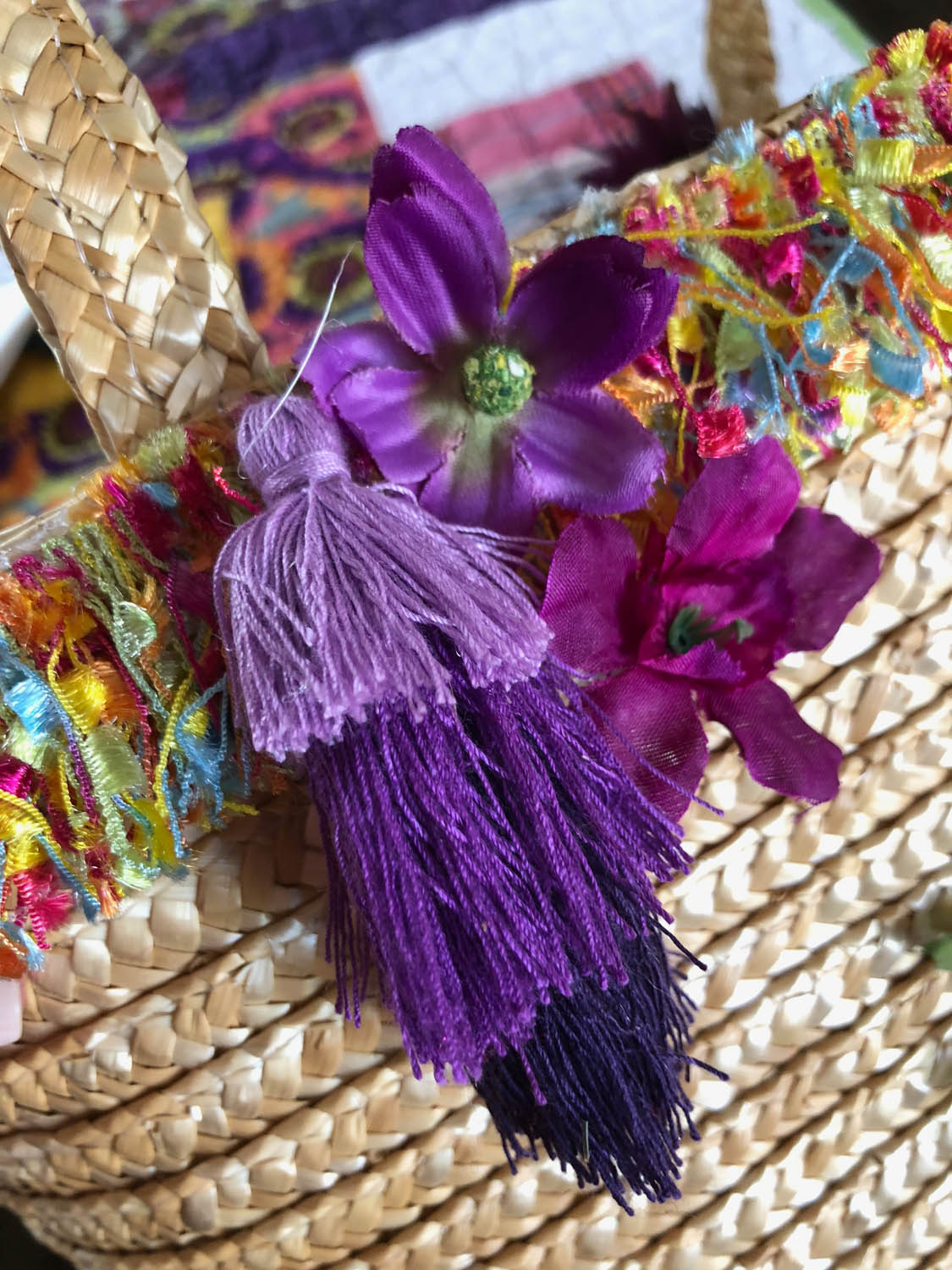 silk flowers and tassels on an embellished straw tote