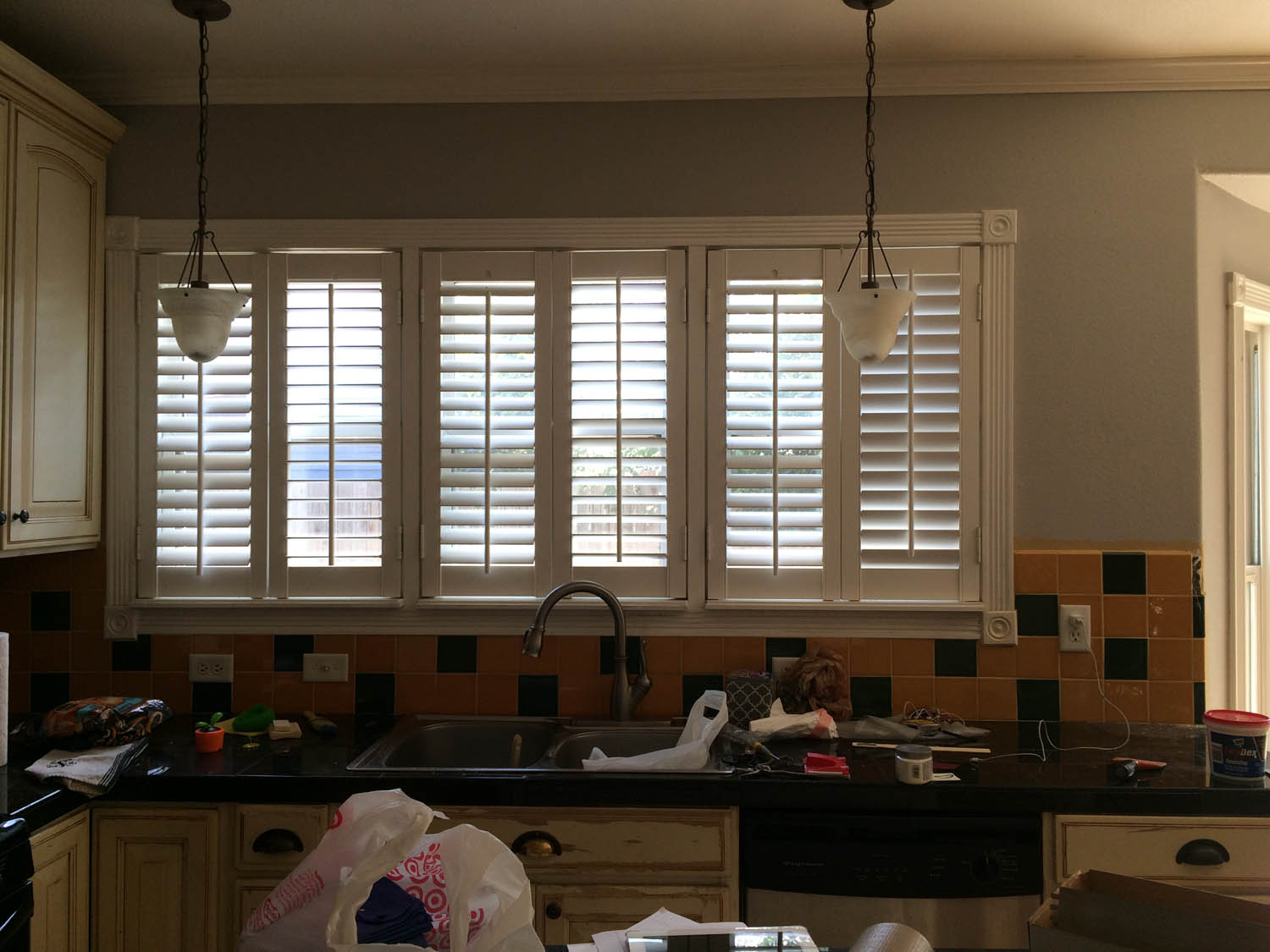 Remodeled kitchen at Curtice Cottage—sink view with old lights and backsplash.