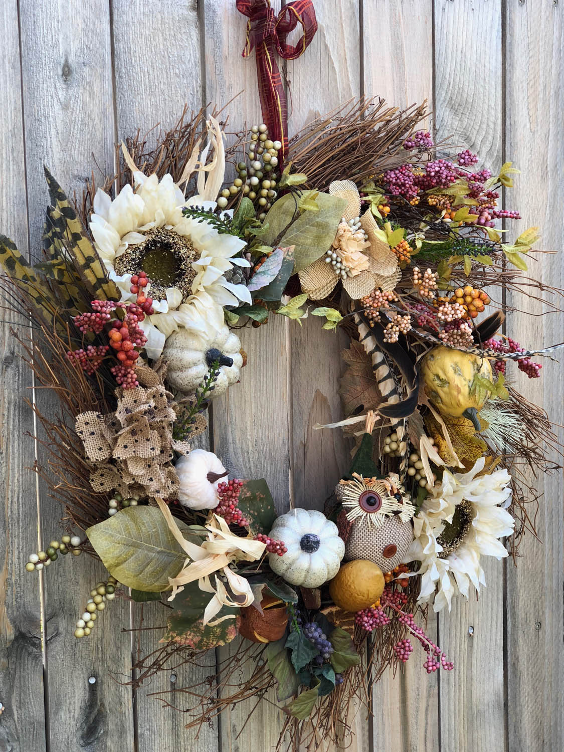 Finished hand made fall wreath hanging on wooden fence outside.