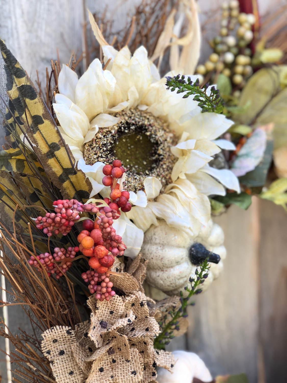 Detail of autumn wreath hanging on wooden fence outside.
