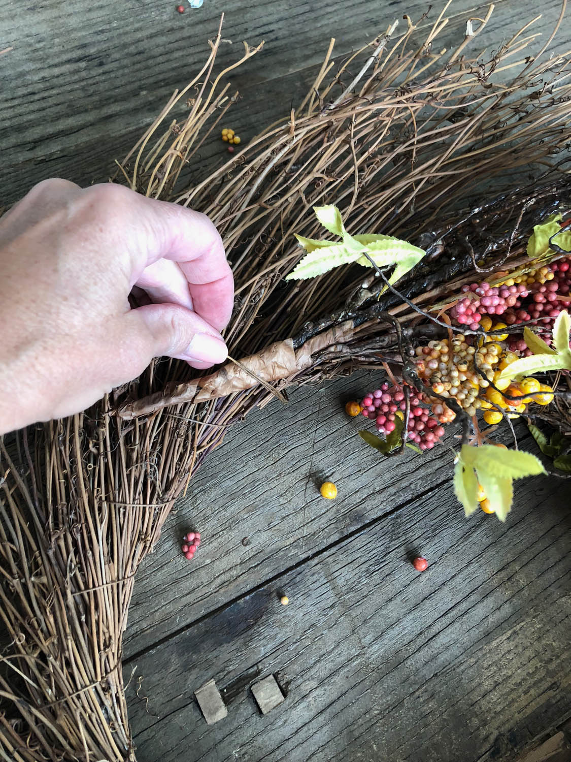 using wire to attach silk flower stems to fall wreath