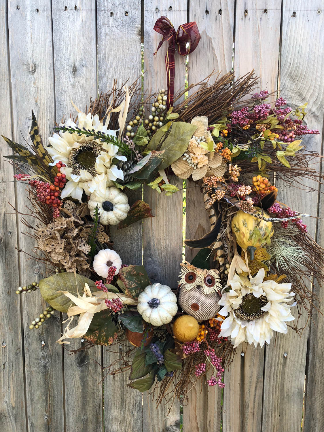 Finished hand made fall wreath hanging on a fence outside.