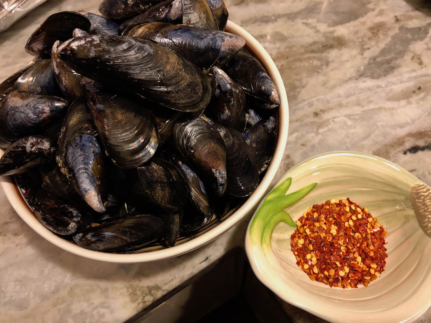 cleaned mussels in a bowl with chili flakes in a prep bowl